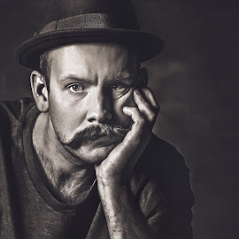 Latency by Bendik Møller - Black & White Portraits & People ( headshot, monochrome, black and white, male, dark background, close up, close, hat, hand, lighting, dark, head, handsome, light, mustache, mono, man )