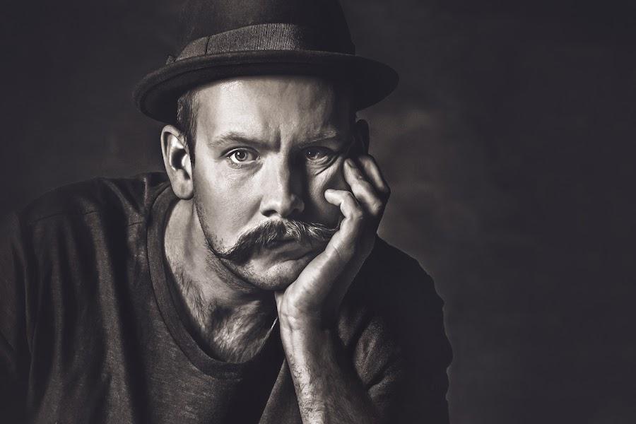 Latency by Bendik Møller - Black & White Portraits & People ( headshot, monochrome, black and white, male, dark background, close up, close, hat, hand, lighting, dark, head, handsome, light, mustache, mono, man )