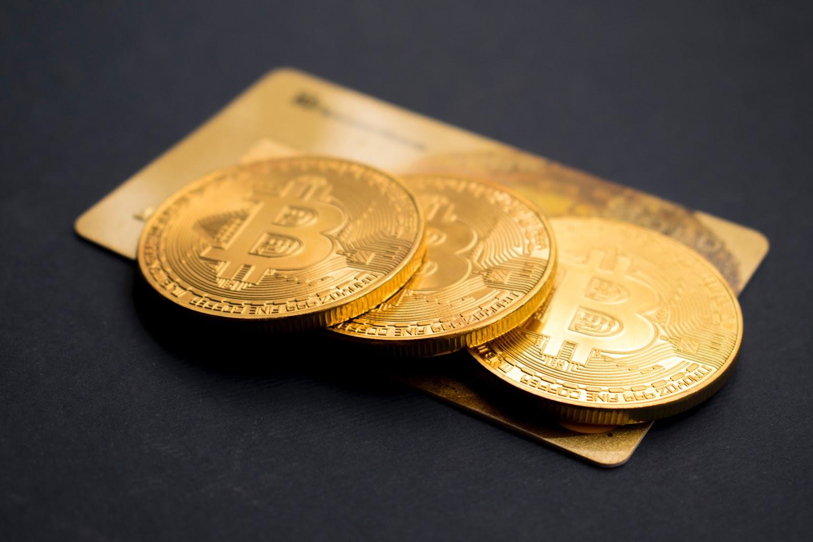 Moedas de Bitcoin sobre um cartão de crédito.