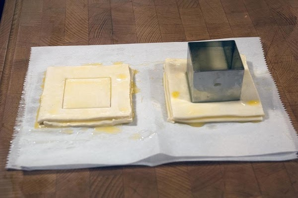 Using a cutting device, cut through the first layer of each Vol au Vent.