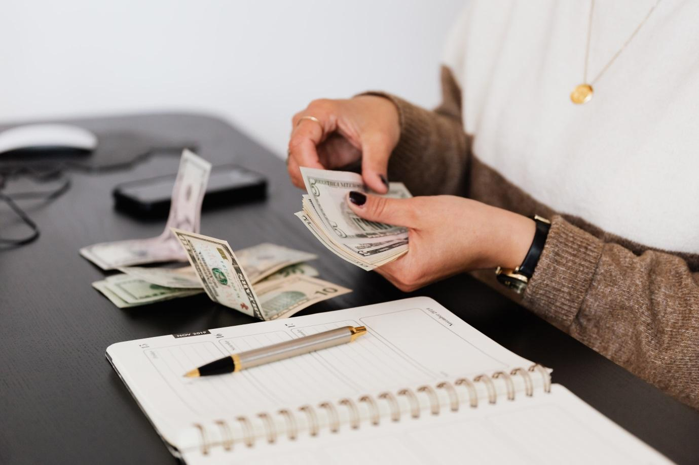 """Photo of a woman counting money; when you budget, you can almost avoid an """"I need money desperately"""" situation"""
