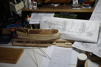 Photo: Next challenge the shear strakes - need to mark waterline, glue three walnut strips together and bend to go around the bow. . . .