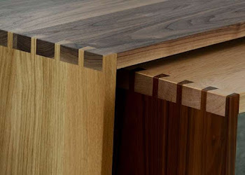 A wooden bench that can fit into storage under a table