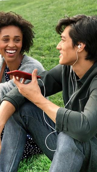 Un hombre y una mujer conversan sentados en una colina cubierta de césped