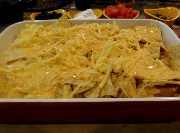 Remove baking dish from oven and add the remaining layer of chips and spoon...