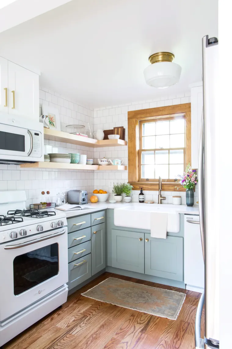 small kitchen with two toned cabinets in light blue grey and white. open shelving makes the space feel bright and airy