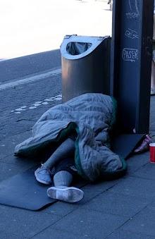Obdachloser liegt neben Papierkorb.