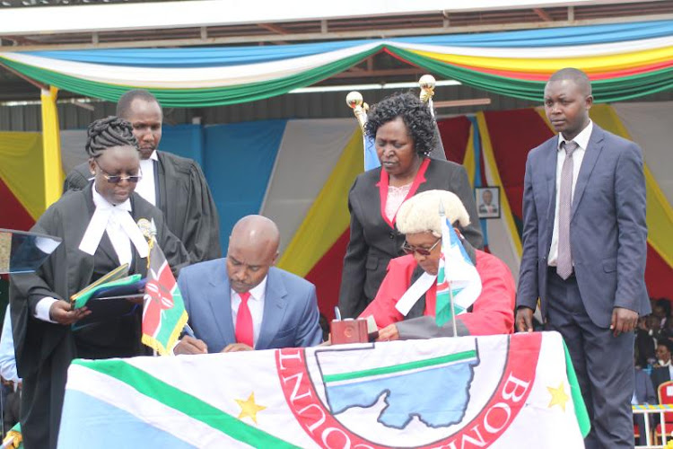 Bomet Governor Dr Hilary Barchok signs certificate of office during the swearing in ceremony as the third at Bomet Green stadium on Thursday on August 8, 2019.