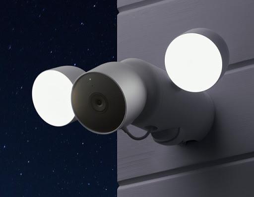 Une NestCam avec projecteur est installée sur le côté d'une <br>maison, et les ampoules éclairent la nuit.