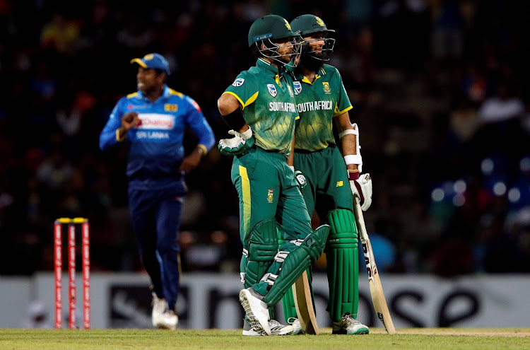 South Africa's Jean-Paul Duminy talks with his teammate Hashim Amla as Sri Lanka's captain Angelo Mathews is seen at the background in Pallekele, Sri Lanka.