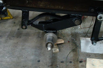 Photo: Photo of left-side, front axle re-installed with new single leaf spring in place. Spring custom fabricated by Malmberg Truck Centre using original spring as a reference.  Photo by J. Loucks