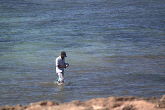Photo: A fisherman walking in after spending time line-fishing on the reef flat