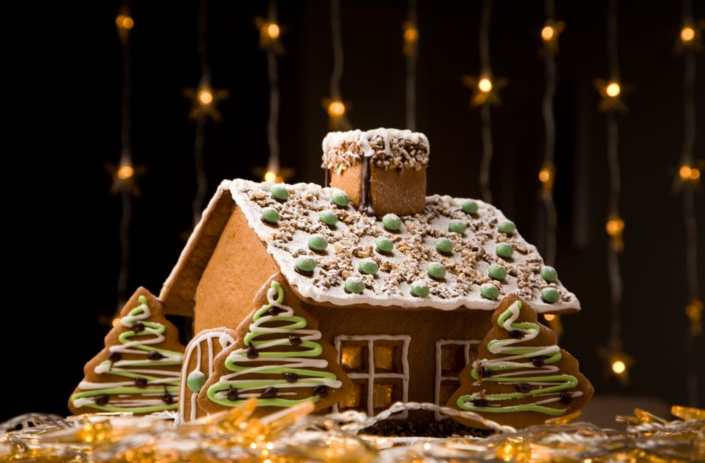 A traditional gingerbread house to display at an apartment against a background of holiday lights.