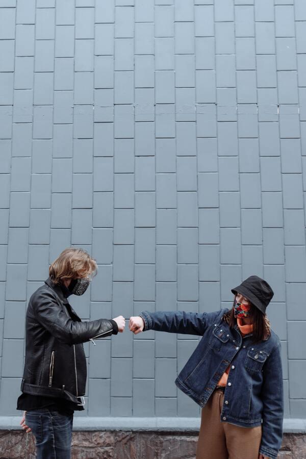 Dois amigos de máscara, se cumprimentando com as mãos, mas mantendo o distanciamento social