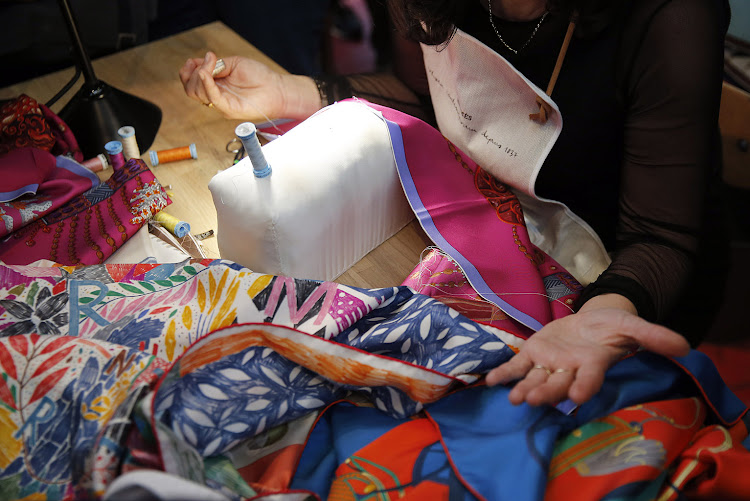 A seamstress works on a scarf of the luxury brand Hermes displayed during the 'Hermes hors les murs' event
