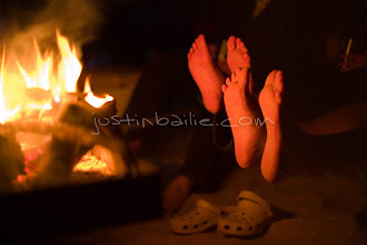 Photo: People warming their feet aound a  campfire while rafting the Grand Canyon. Grand Canyon NP, AZ.