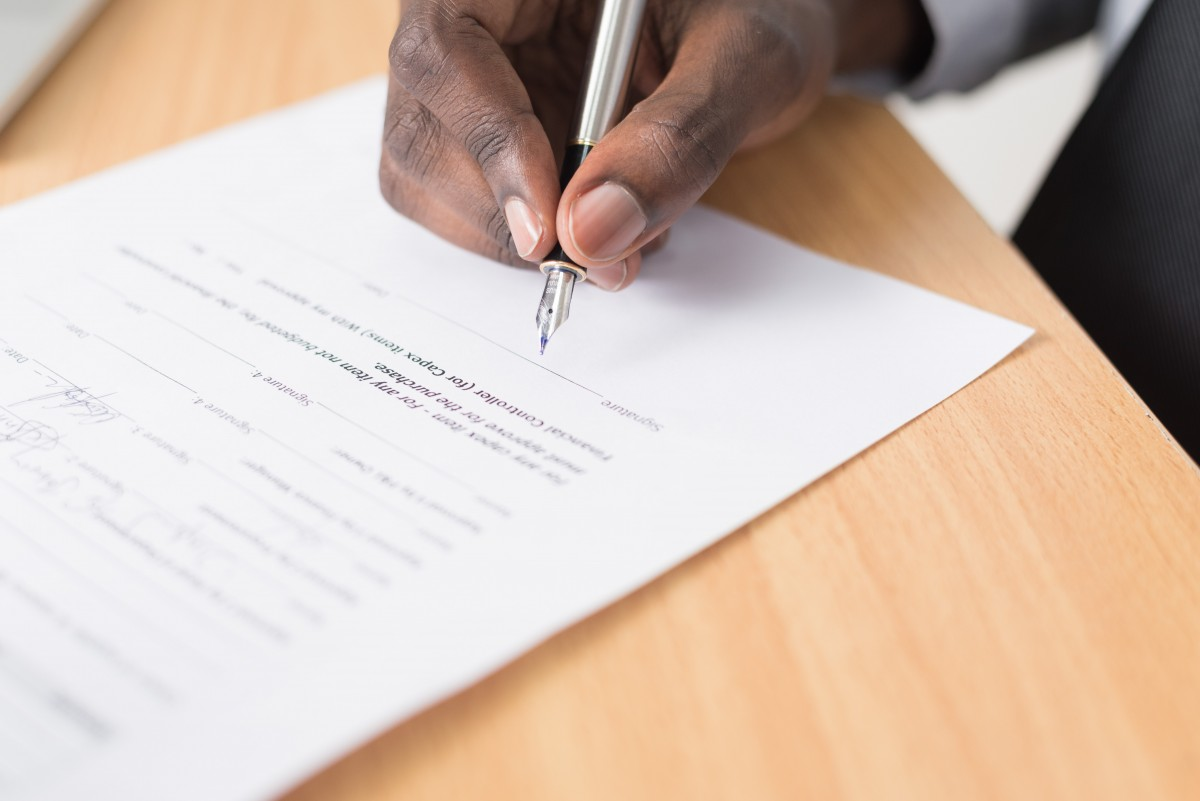 de cerca contrato escritorio documento mano escritura oficina papel papeleo bolígrafo persona firma firma mesa escritura