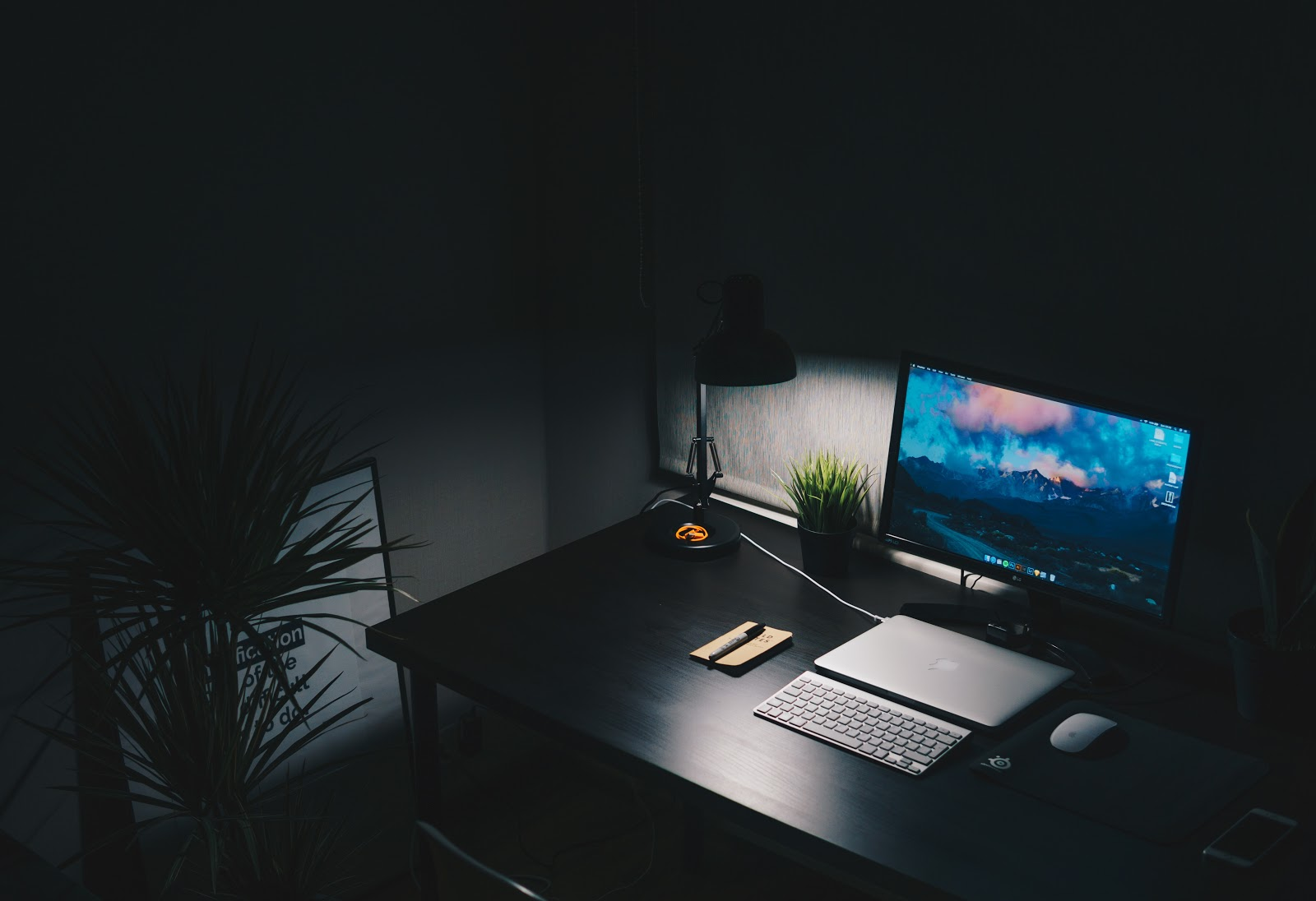 Dark room with a desk and a computer.