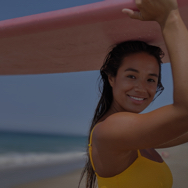 Woman wearing yellow swimsuit, holding surfboard over her head
