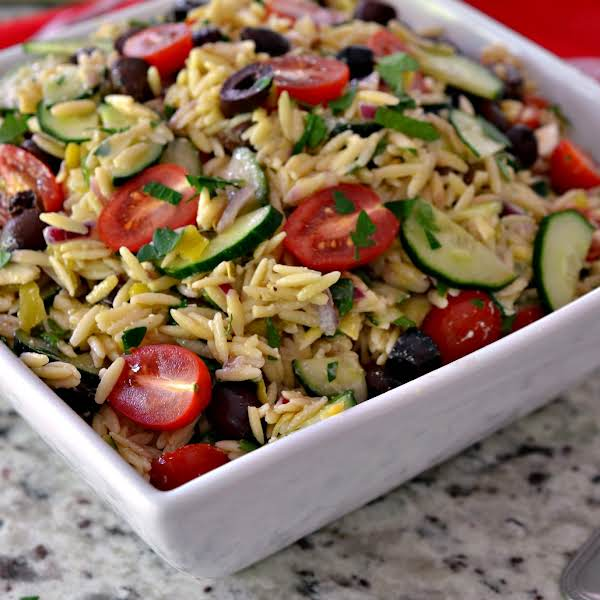 Greek Orzo Salad Is A Flavor Packed Pasta Salad That Can Be Cooked And On The Table In Less Than Thirty Minutes.  It Is Packed Full Of Some Of Natures Best Ingredients And Drizzled With A Light Lemon Vinaigrette.