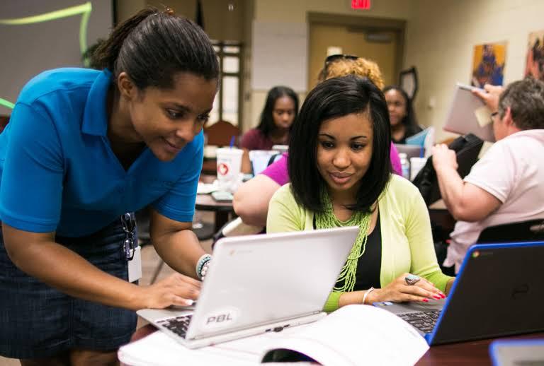 Duas mulheres estão olhando para a tela de um laptop.