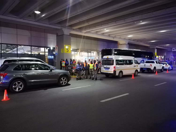 Police and security personnel wait at the OR Tambo International Airport in Johannesburg for the much anticipated arrival of Spanish giants FC Barcelona. The La Liga champions are scheduled to play an international friendly match against South African champions Mamelodi Sundonws at FNB Stadium on Wednesday May 16 2018.