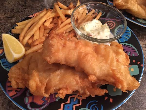 Two Pieces Of Battered Fish On A Plate With French Fries, Tartar Sauce And A Lemon Wedge.