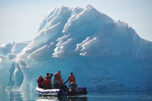 Uncruise-skiff-iceberg.jpg - A skiff from an UnCruise Adventures expedition explores an iceberg in Alaska.