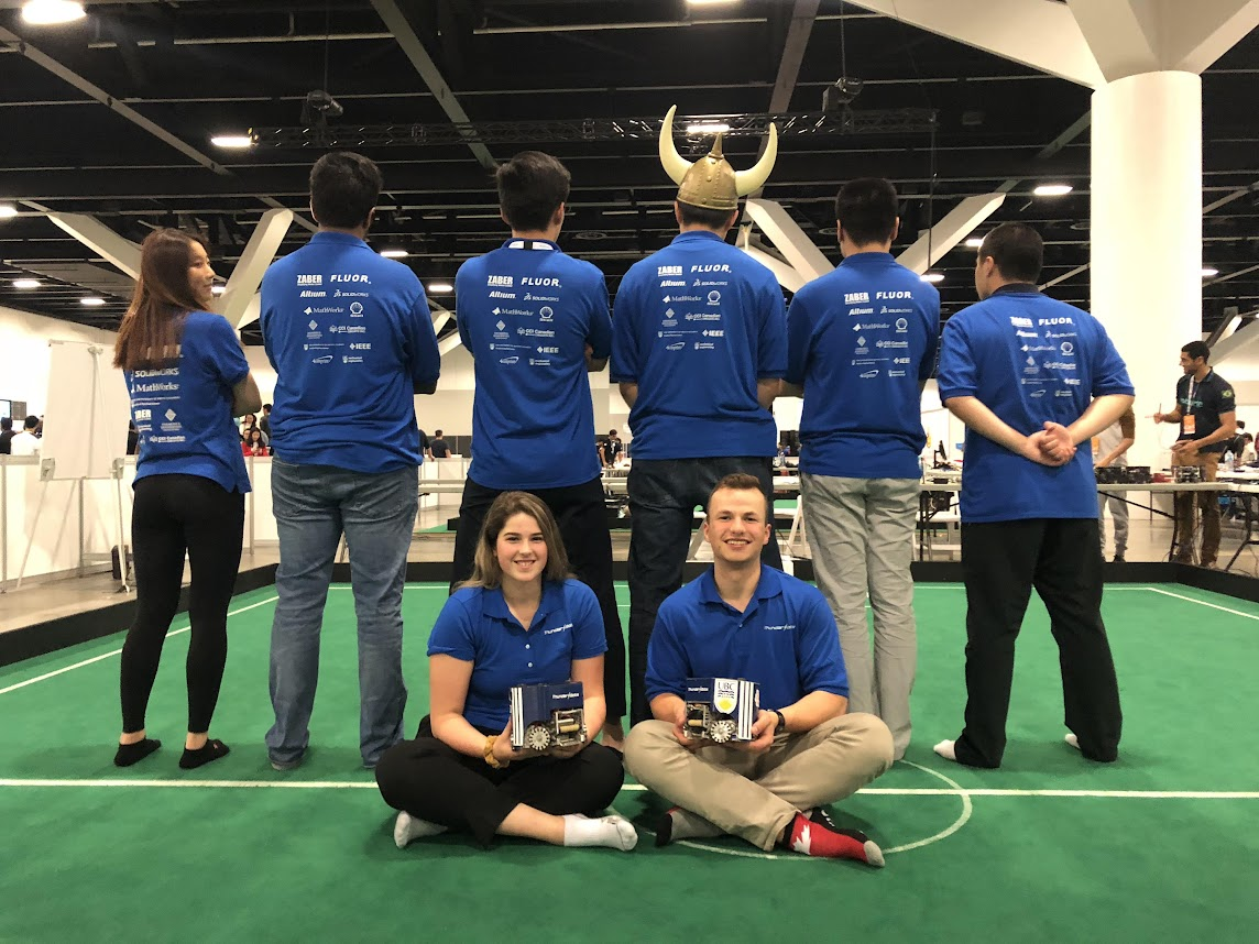 Students in robotics showing the back of their blue shirts with two students holding awards