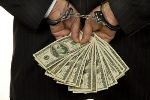 Man with handcuffs holding dollar notes behind his back