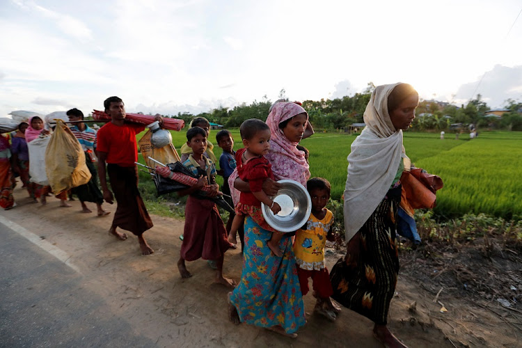 Rohingya refugees, who arrived from Myanmar on Sunday night, walk in a rice field after crossing the border in Palang Khali, Bangladesh, on Monday. Picture: REUTERS