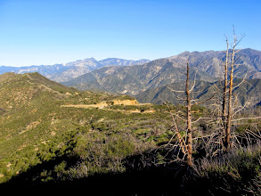 Photo: View west from the switchback toward the trailhead. Twin Peaks East Peak is the pointed summit on the left horizon while Hawkins Ridge dominates the horizon on the right.