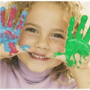 Little girl with fingerpaint on hands smiling