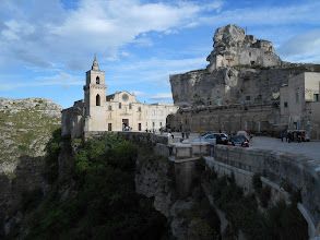 Photo: Matera Duomo in the background, with cliff dwellings built into the rocks.