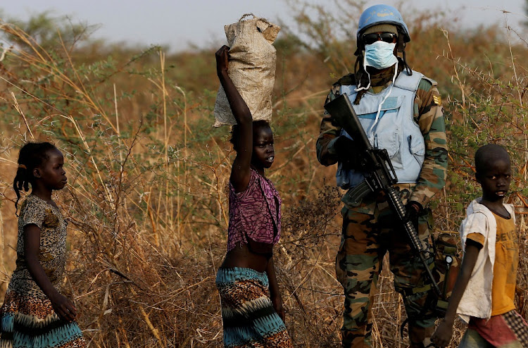 A UN peacekeeper stands guard as children walk by in South Sudan. Picture: REUTERS