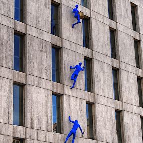 Climbing the wall by Cathleen Steele - Artistic Objects Other Objects ( sculptures, climbers, surreal, blue, background, imagery, amusing, wall, building )