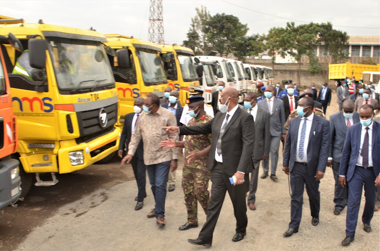 President Uhuru Kenyatta and NMS DG Major General Mohamed Badi when the head of state flagged off a fleet of vehicles rehabilitated by the Nairobi Metropolitan Services on October 7