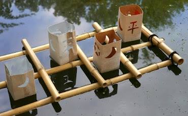 Schwimmlichter aus Getränkepackung mit japanischen Zeichen und Symbolen auf Bambusgitter.