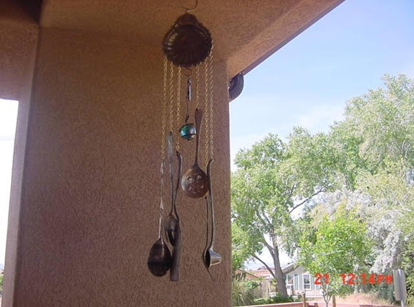 This is the large windchime, which consists of a candy dish as a base, and light weight chains, which will rust to perfection some day.  They hold silver pieces: 2 serving forks, 1 serving spoon, salad tongs, serving spatula, and a candle lopper. The blue ball was on an old wind spinner we had for years that fell apart.  The whole chime cost under $5 to make.