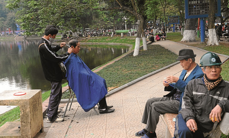 A street barber serves a customer at a public park in downtown Hanoi. Vietnam is abuzz with political gossip ahead of a key leadership change this week that has plunged the ruling communist elite into turmoil. Picture: GALLO IMAGES/AFP/LOUISA GOULIAMAKI