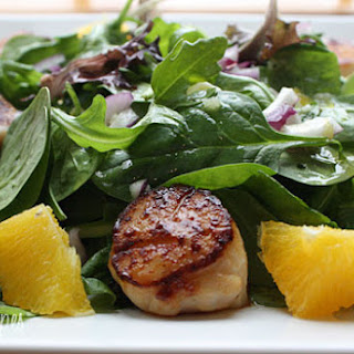 Pan Seared Scallops with Baby Greens and Citrus Mojo Vinaigrette.