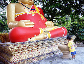 Photo: Big & Small #TravelThursday :- I spotted this child playing with the lilies & the water at the foot of this big round Buddha image in Wat Chedi Luang, Chiang Mai, Thailand. Since this shot was taken they have removed the pot the child is playing with and built a room around the Buddha image changing it completely.  Photography by Justin Hill ©