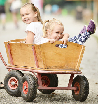 Two little girls riding in wagon