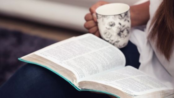 Woman praying calming prayer with Bible and coffee