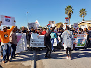 "About 60 people with placards reading ""Homophobia hurts"" and ""Stop killing our brothers and sisters"" marched through the streets of Gugulethu to the police station in Manenberg on Friday."