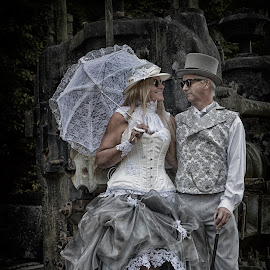 by Marco Bertamé - People Couples ( sunglasses, couple, woman, steampunk, white, umbrella, goggles, robe, hat, man, two, grey )