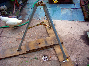 Photo: This is a scavenged tripod base we used for a 10foot+ rooftop mast.  The wood is just spare, treated lumber that was sitting around handy, fastened with 1/4in bolts. As evident in the photo, the hen approves of this construction.