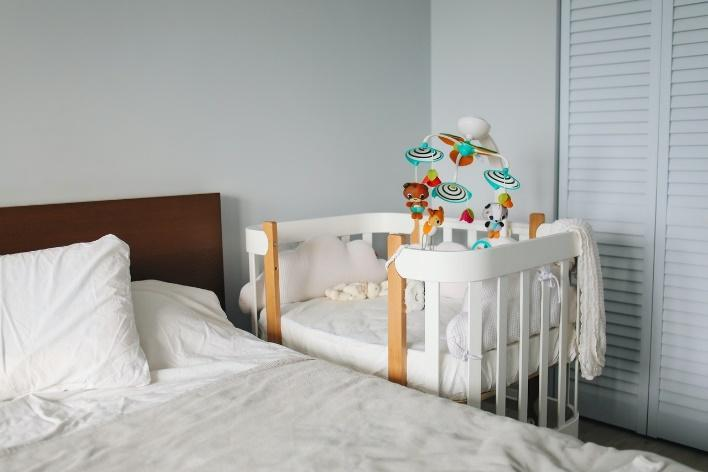 Baby crib attached to a bed, one of the best space-saving hacks for new parents.