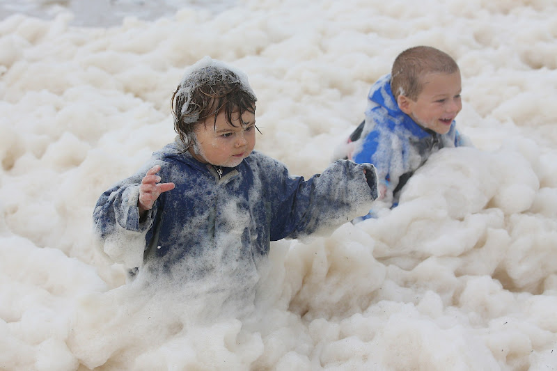 Photo: GOLD COAST, AUSTRALIA - JANUARY 28:  Children play with ocean foam in Burleigh Heads as Queensland experiences severe rains and flooding from Tropical Cyclone Oswald on January 28, 2013 in Gold Coast, Australia. Hundreds have been evacuated from the towns of Gladstone and Bunderberg while the rest of Queensland braces for more flooding.  (Photo by Chris Hyde/Getty Images)