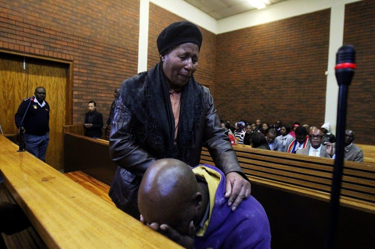 Sibusiso Emmanuel Tshabalala is comforted during a court appearance after he shot dead his son Luyanda earlier this year.